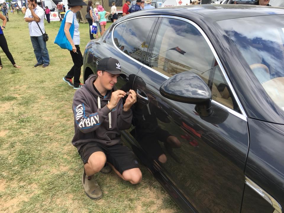 Locksmith unlocking a locked car.